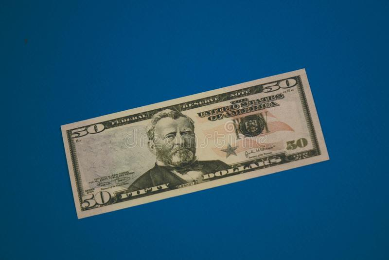 Banconota in dollari isolata dell'americano cinquanta su fondo blu immagine stock libera da diritti
