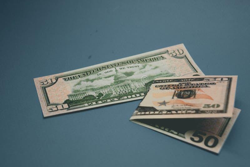 Banconota in dollari isolata dell'americano cinquanta su fondo blu fotografia stock