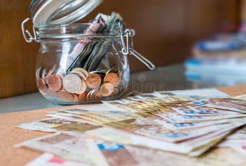 Banconota e monete in barattolo di vetro immagini stock libere da diritti