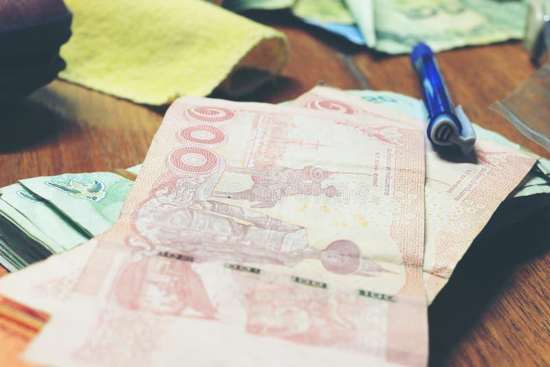 Banconota tailandese dei soldi e del calcolatore con la carta bianca del taccuino, penna sull'ufficio di legno della tavola a cas fotografia stock