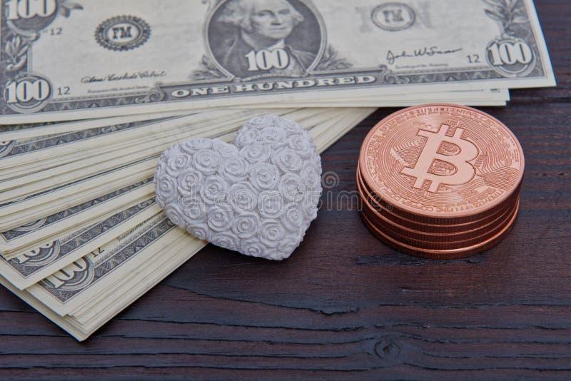 Banconote, bitcoins e cuore del dollaro su una tavola immagine stock libera da diritti