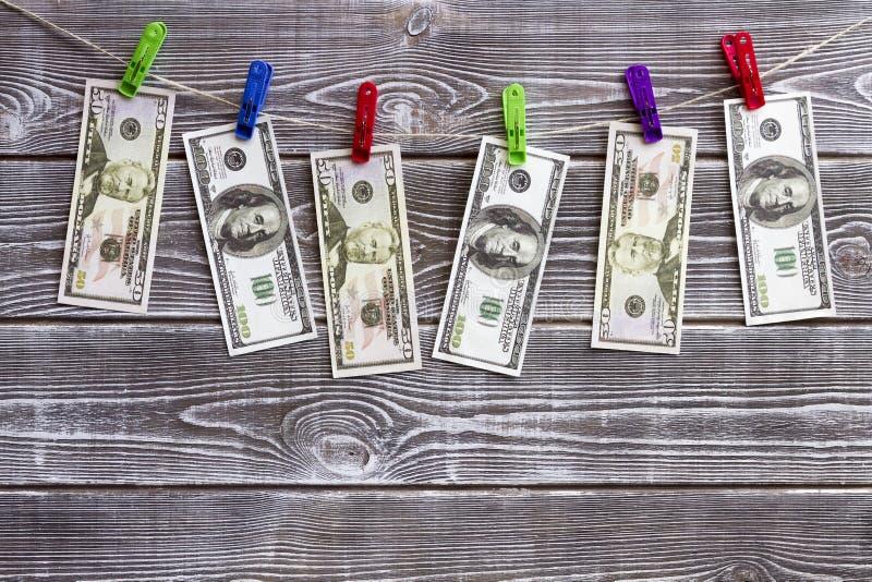 Banconote dei dollari che appendono su una corda sulle mollette da bucato fotografia stock libera da diritti