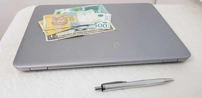 Banconote dei dynars di hryvnia e dollari posti sopra il computer portatile fotografia stock libera da diritti