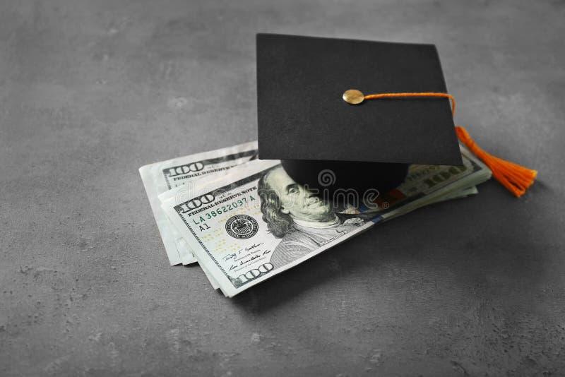 Banconote del cappello e del dollaro di graduazione sulla tavola immagini stock libere da diritti