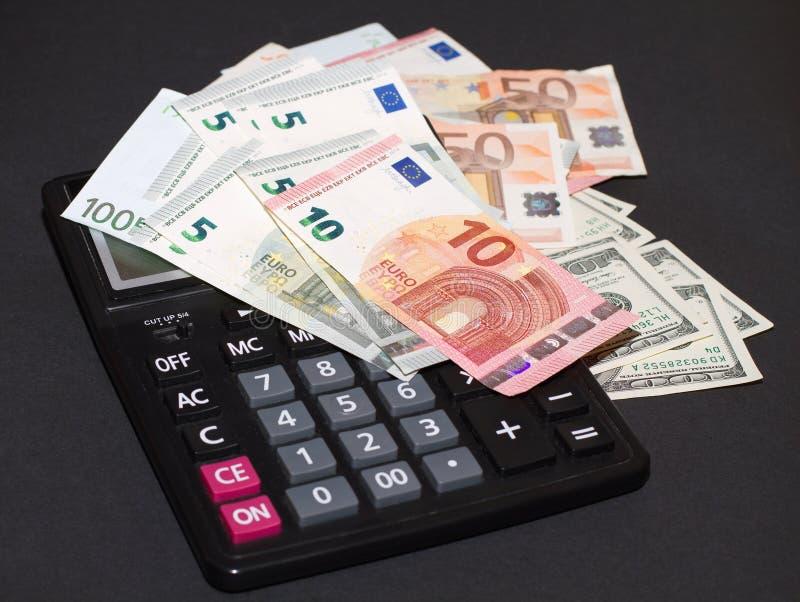 Banconote di soldi europei ed americani e della calcolatrice su fondo nero immagini stock libere da diritti