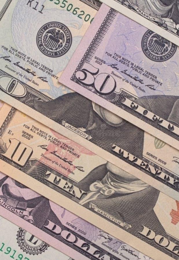 Banconote in dollari americane astratte del fondo differente di denominazione fotografia stock