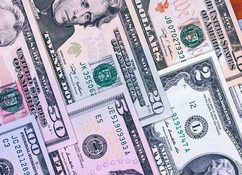 Banconote in dollari americane astratte del fondo differente di denominazione fotografie stock