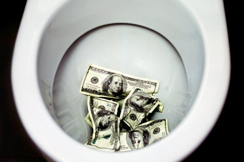 Banconote in dollari dei tiri nella toilette immagine stock libera da diritti