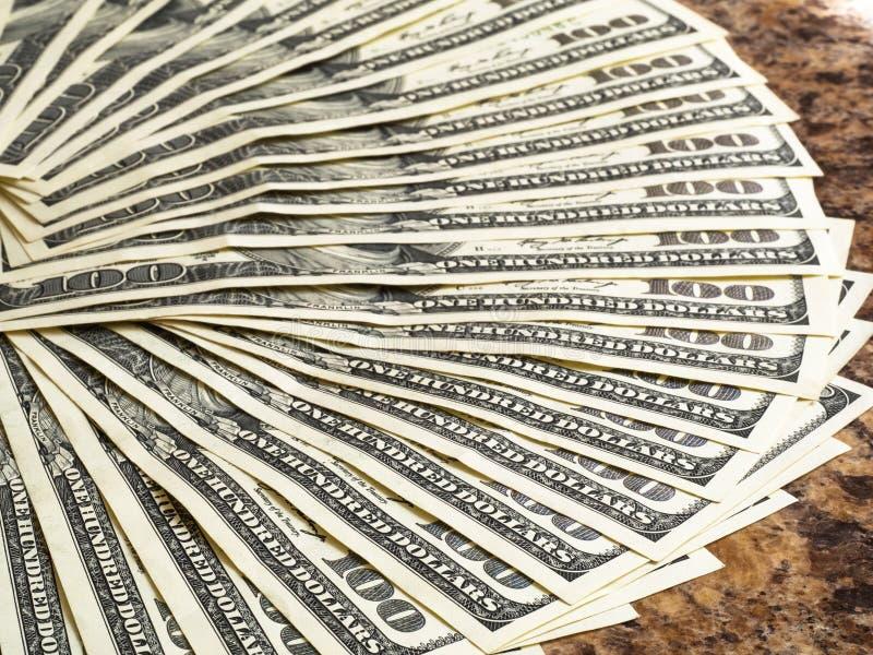 100 banconote in dollari impilate sulla tavola fotografia stock
