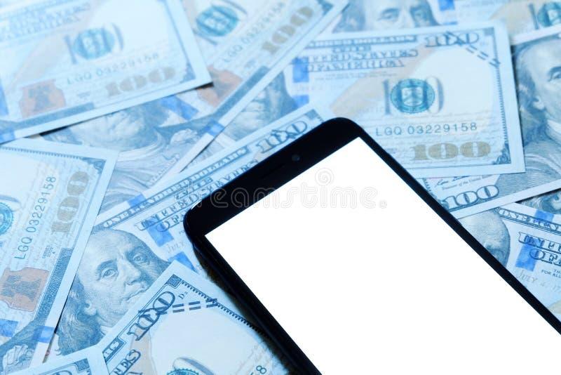 Banconote in dollari o banconote con lo smartphone o il telefono cellulare con fondo bianco dello spazio della copia per testo o  immagine stock libera da diritti