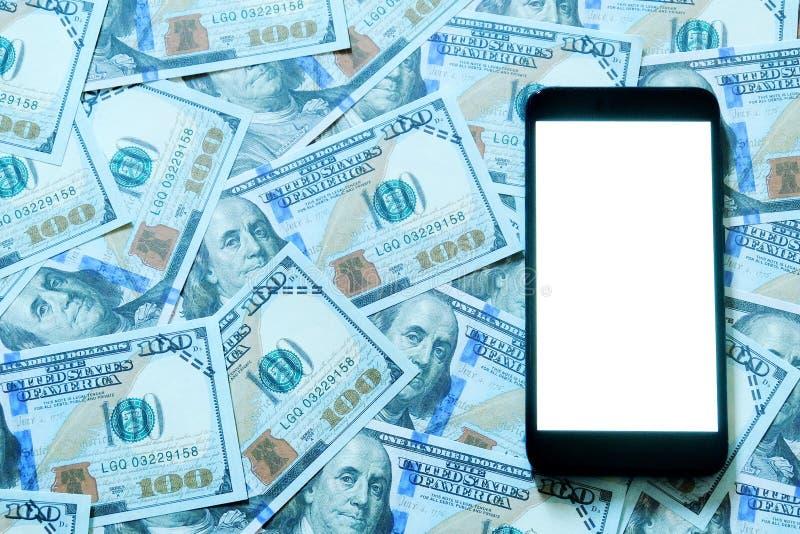 Banconote in dollari o banconote con lo smartphone o il telefono cellulare con fondo bianco dello spazio della copia per testo o  immagini stock libere da diritti