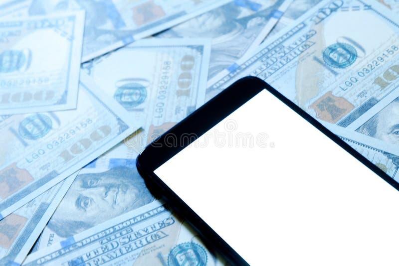 Banconote in dollari o banconote con lo smartphone o il telefono cellulare con fondo bianco dello spazio della copia per testo o  fotografia stock