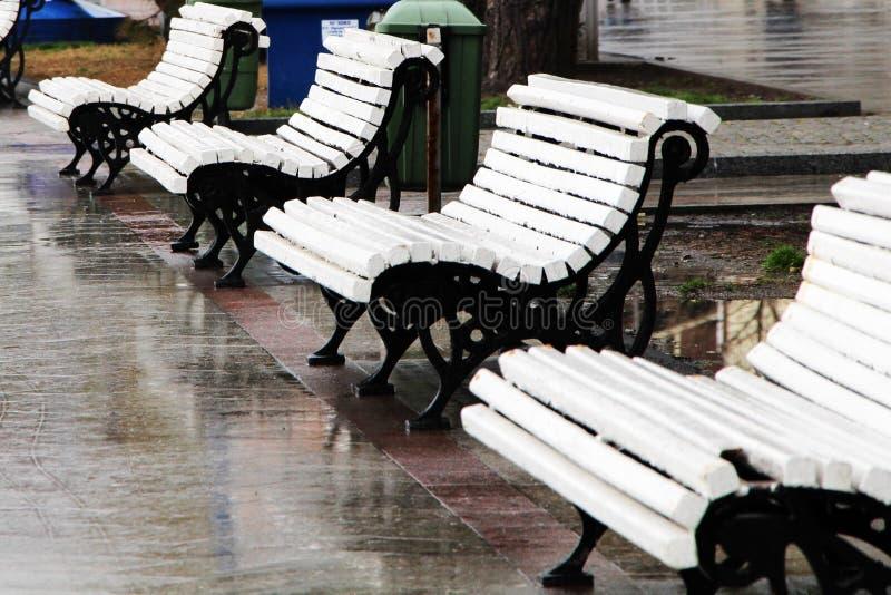Bancos blancos en la calle cerca del terraplén después de la lluvia foto de archivo