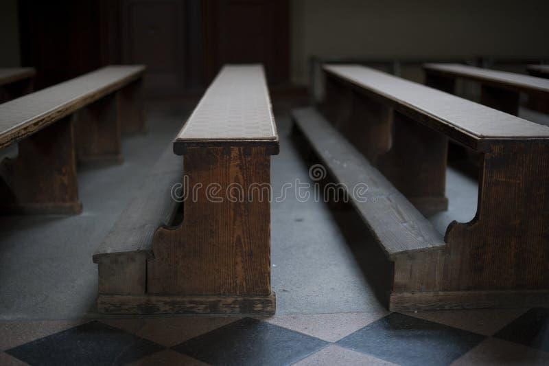 Bancos de madera de la iglesia vieja con la luz pobre en iglesia vacía en Zagreb fotografía de archivo libre de regalías