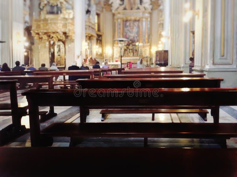 Bancos de madera a sentarse dentro de una iglesia católica barroca durante la liturgia fotos de archivo
