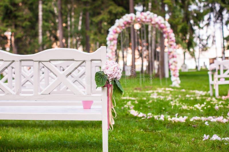 Bancos do casamento e arco da flor para a cerimônia fotos de stock royalty free
