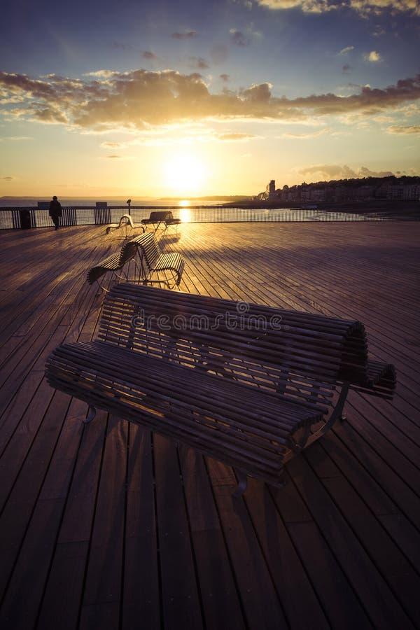 Bancos en el nuevo embarcadero de Hastings en la puesta del sol fotografía de archivo libre de regalías