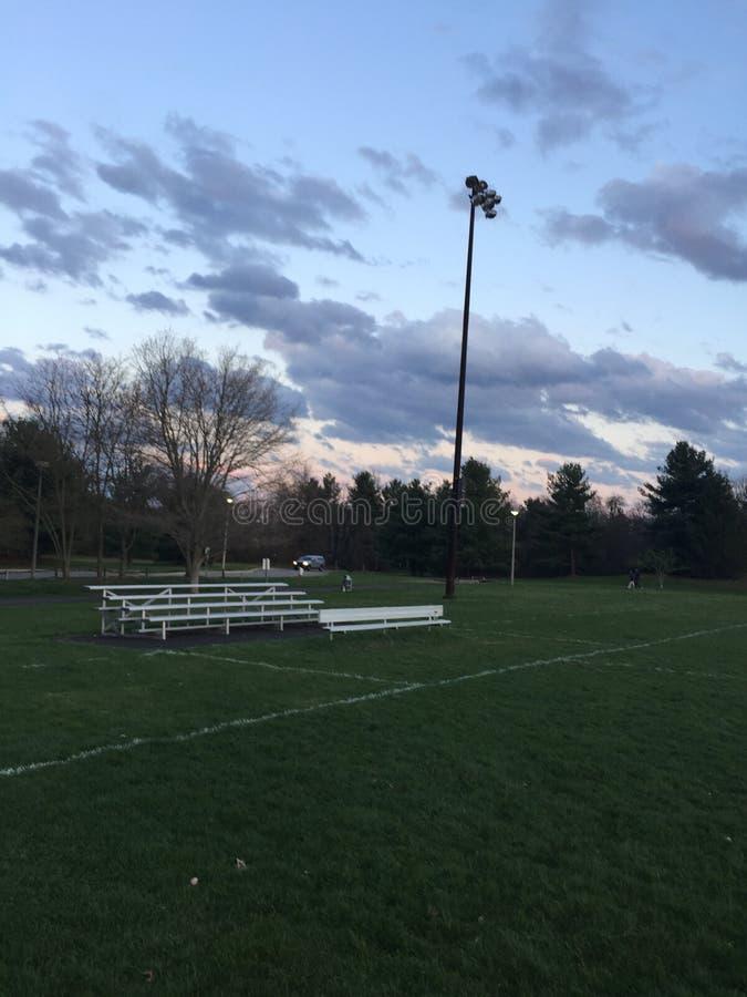 Bancos espectadores: campo de futebol no crepúsculo na mola adiantada imagem de stock