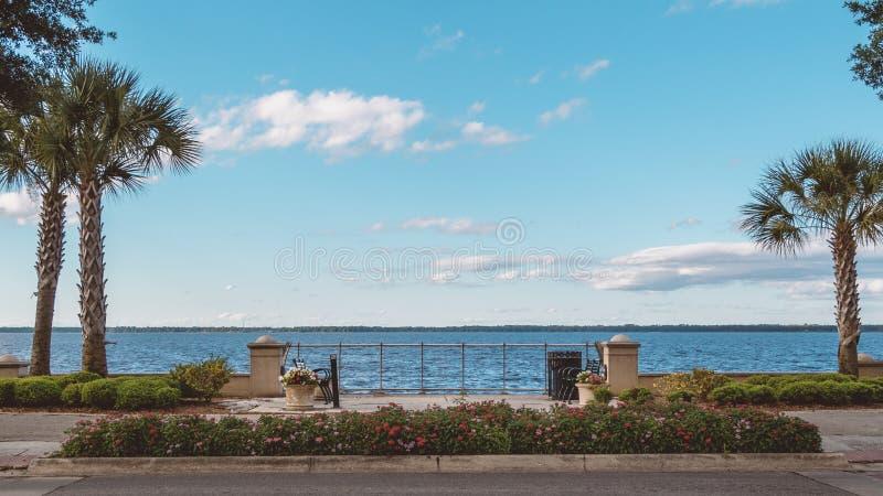 Bancos frente al mar en el lago Monroe, en la histórica ciudad de Sanford, Florida fotografía de archivo