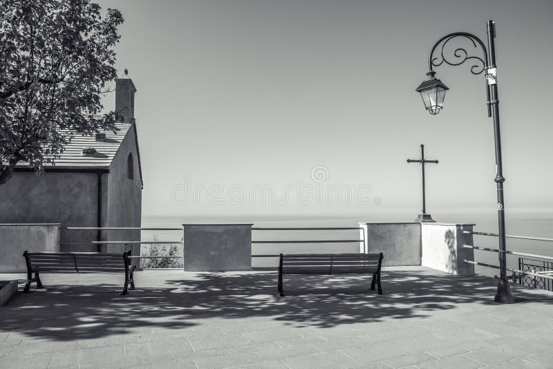Bancos, lookin simple de la iglesia y de la cruz sobre mediterráneo fotos de archivo
