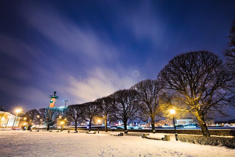 Bancos sob a neve ao longo da passagem, das árvores e das luzes de rua na terraplenagem Arquitetura da cidade do inverno no crepú imagem de stock