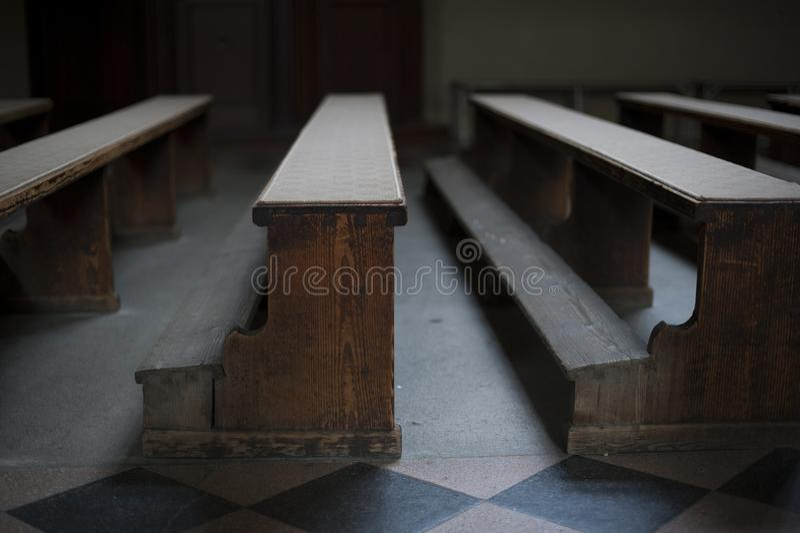Bancs en bois de vieille église avec la lumière pauvre dans l'église vide à Zagreb photographie stock libre de droits