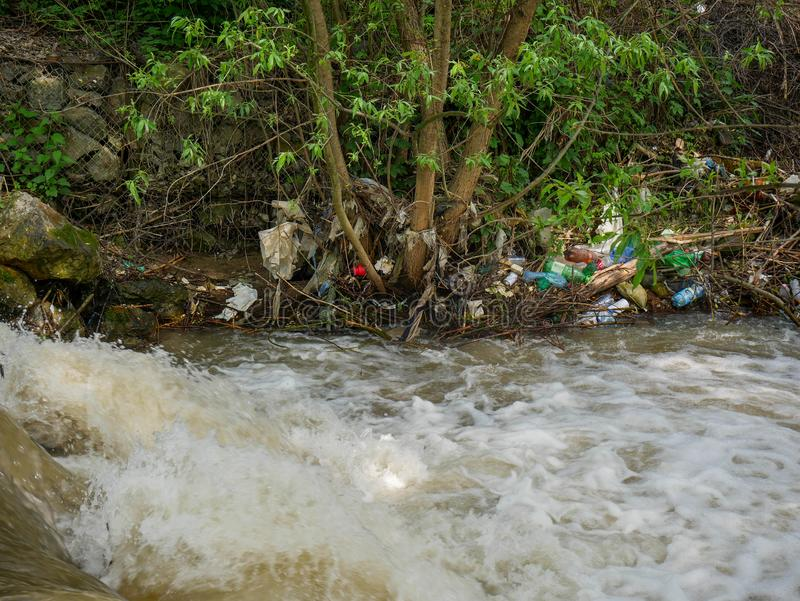 Plastic bottles and human trash in the river, conceptual human negligence image. Bancu, Romania- 20 May 2019: Plastic bottles and human trash in the river stock photos
