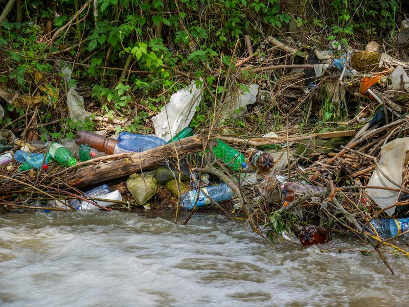Plastic bottles and human trash in the river, conceptual human negligence image. Bancu, Romania- 20 May 2019: Plastic bottles and human trash in the river royalty free stock image