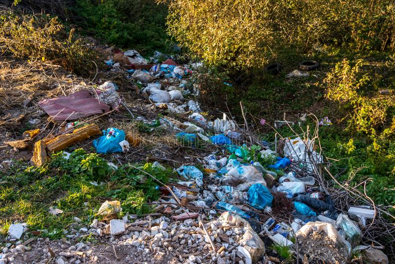 Clean little creek polluted with human trash, conceptual image of human negligence. Bancu, Romania- 08 October 2018: Clean little creek polluted with human stock images