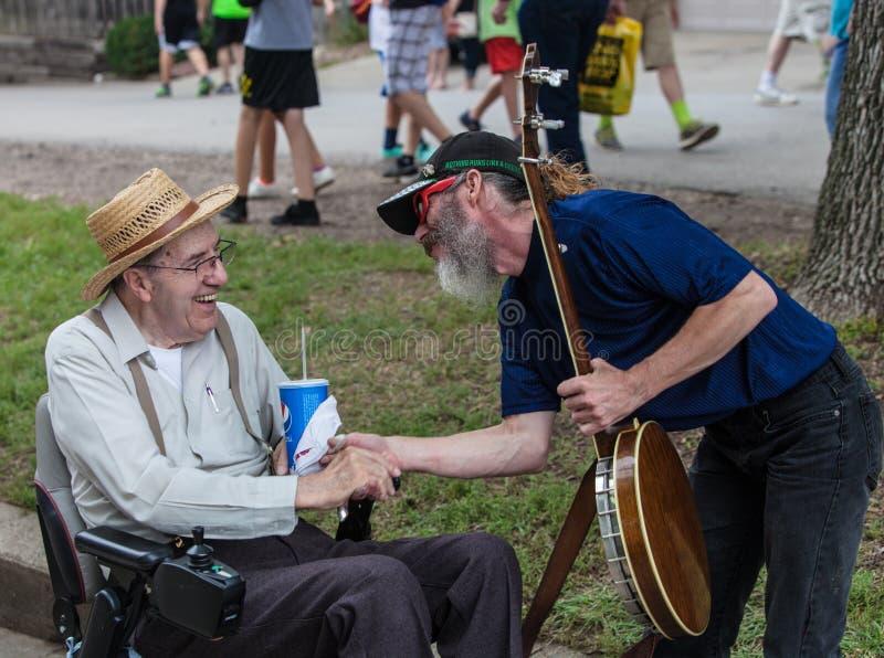 Bandżo gracz z mężczyzna w wózku inwalidzkim przy Iowa stanu jarmarkiem zdjęcie royalty free