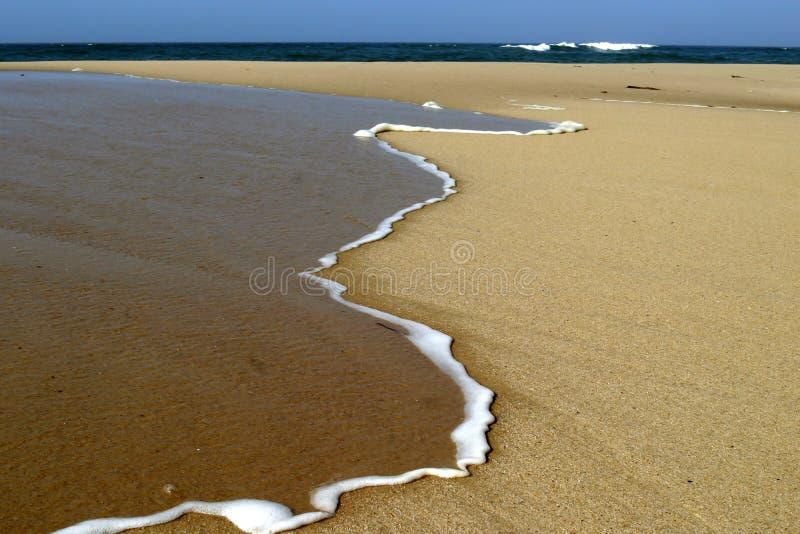 Band av skum på sand arkivfoton