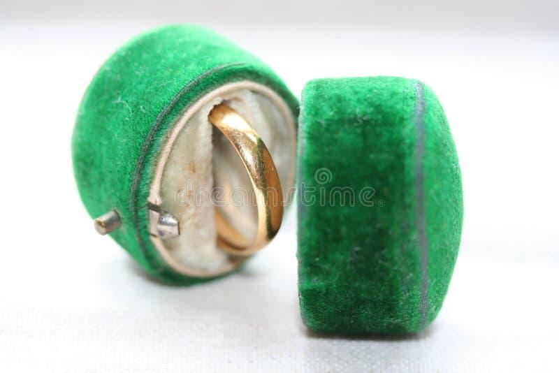 Band der goldenen Hochzeit im antiken grünen Samtkasten stockfotografie