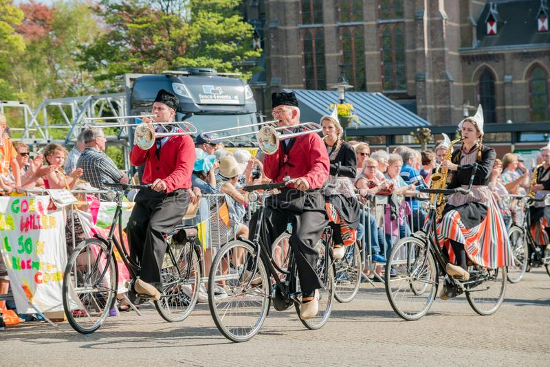 Band dress up and ride bicycle performancing music in the beautiful and colorful flower parade royalty free stock image