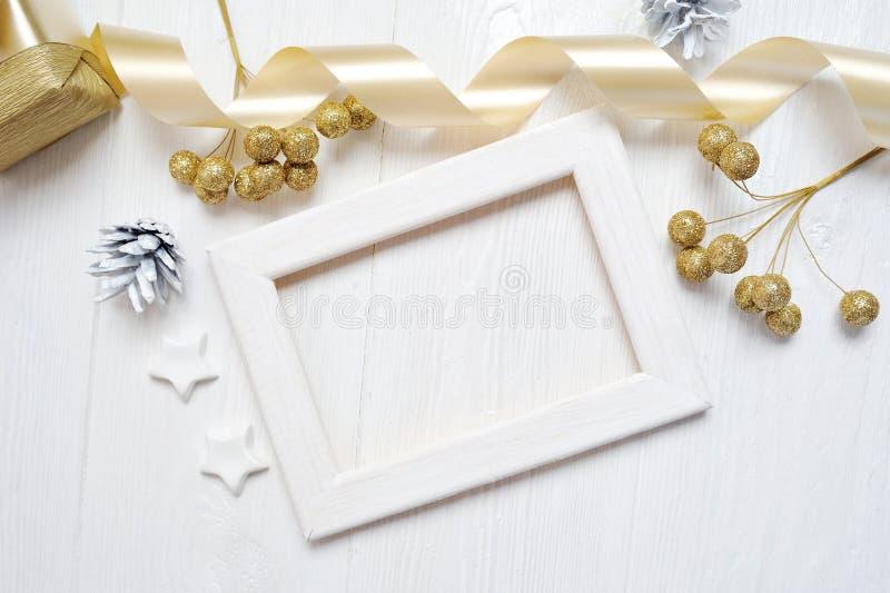 Band för pilbåge för wood ram för modelljul guld- och trädkotte som är flatlay på en vit träbakgrund, med stället för ditt fotografering för bildbyråer