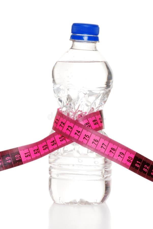 Band-Maß um Wasser-Flasche stockbild