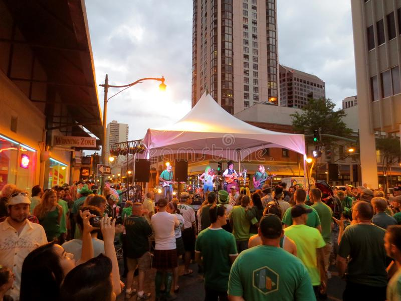 Band plays on stage as crowd watches at St. Patrick's Day Block Party in street royalty free stock image