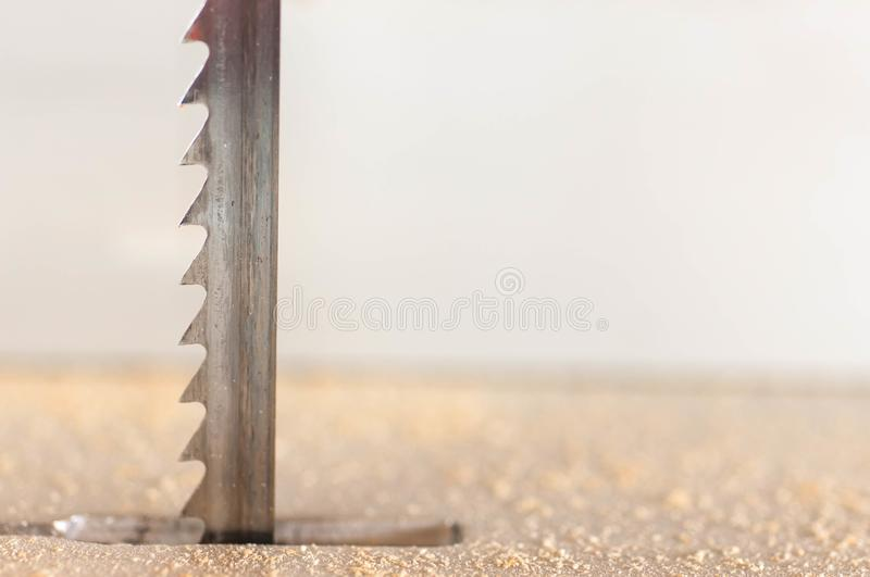 Band saw blade close up macro shot. Wood chip on the foreground royalty free stock photo