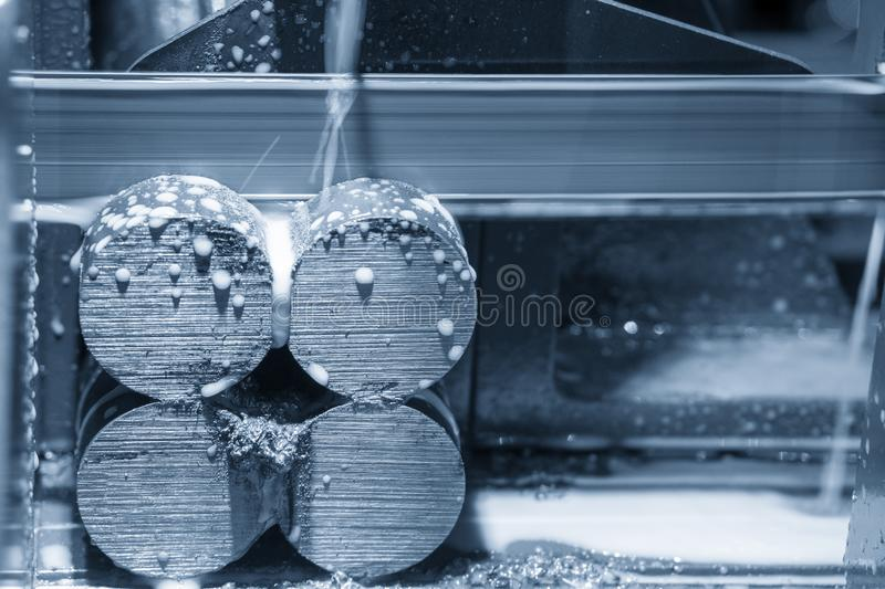 The band saw machine cutting the metal rod. The metal cutting process by band saw machine with coolant method stock image
