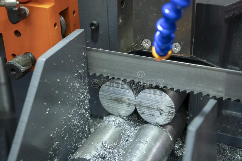 The band saw machine cutting raw metals rods. The with the coolant fluid.The industrial sawing machine cutting the material rod stock photos