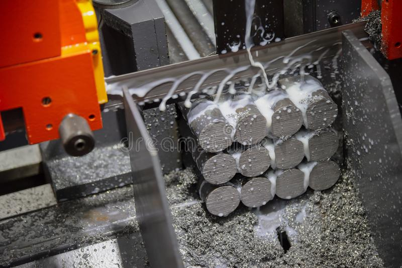 The band saw machine cutting raw metals rods. The with the coolant fluid.The industrial sawing machine cutting the material rod stock photo