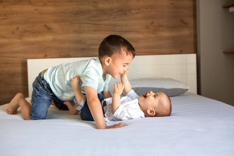 Band of two brothers on the couch. Playing together with joy and cheerfulness royalty free stock photos