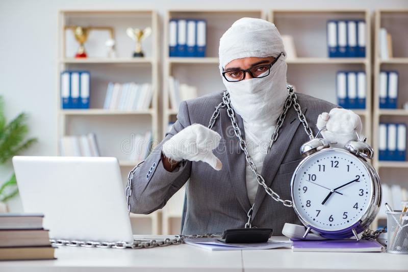 Bandażujący biznesmena pracownik pracuje w biurowym robi paperwor obraz stock