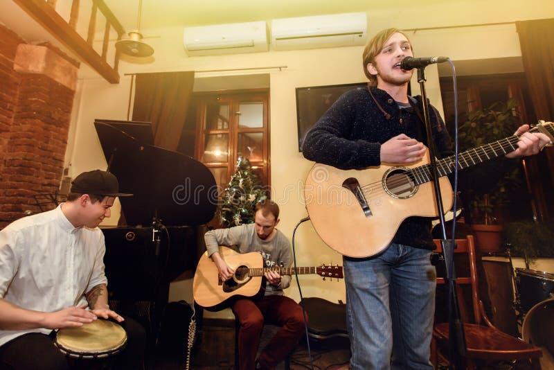 Banda acústica elegante de los hombres jovenes que juegan y que cantan en un macho fotografía de archivo libre de regalías