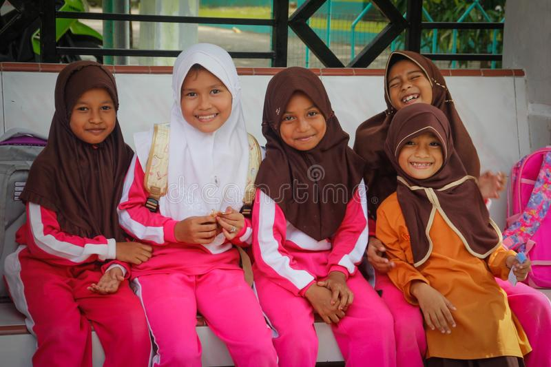 Little Indonesian kids girls in hijabs are waiting for the school bus at the bus stop stock photo