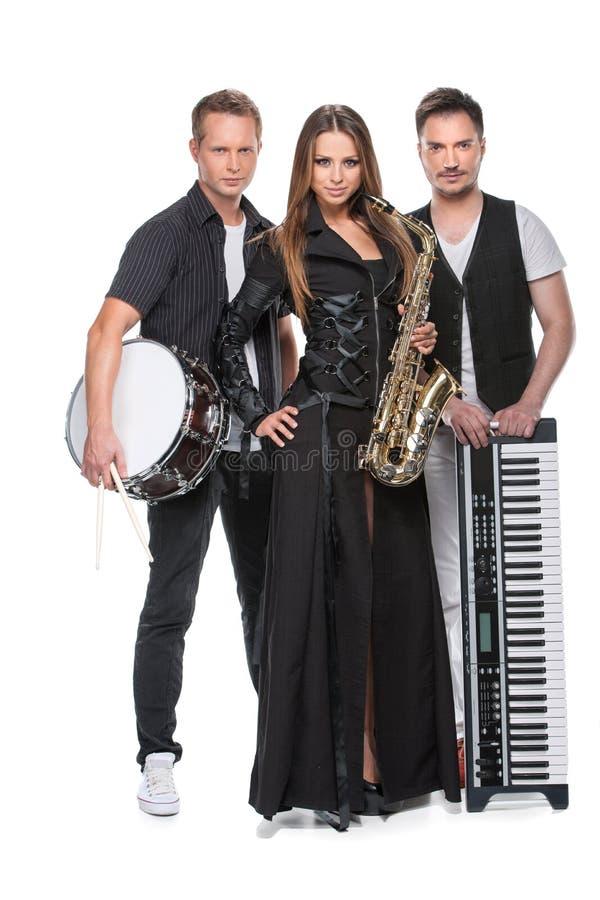 Banda atractiva elegante que presenta así como los instrumentos de música. imagen de archivo libre de regalías