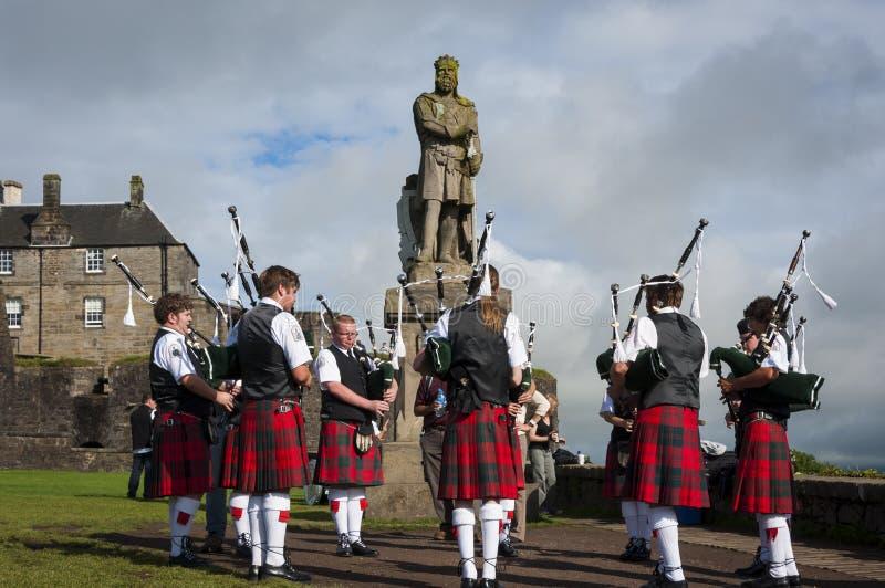 Banda de los gaiteros que juegan delante de la estatua de Roberto al Bruce en Stirling Castle en Stirling, Escocia imágenes de archivo libres de regalías