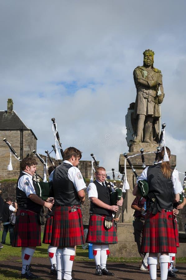 Banda de los gaiteros que juegan delante de la estatua de Roberto al Bruce en Stirling Castle en Sirling, Escocia imagen de archivo libre de regalías