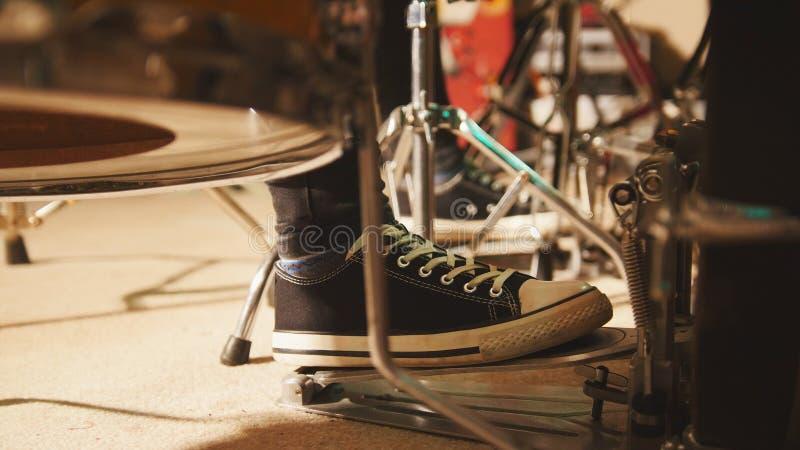 Banda de rock que ensaya en el garaje - el pie del ` s del batería lleva las zapatillas de deporte que mueven el pedal del bajo d imagenes de archivo