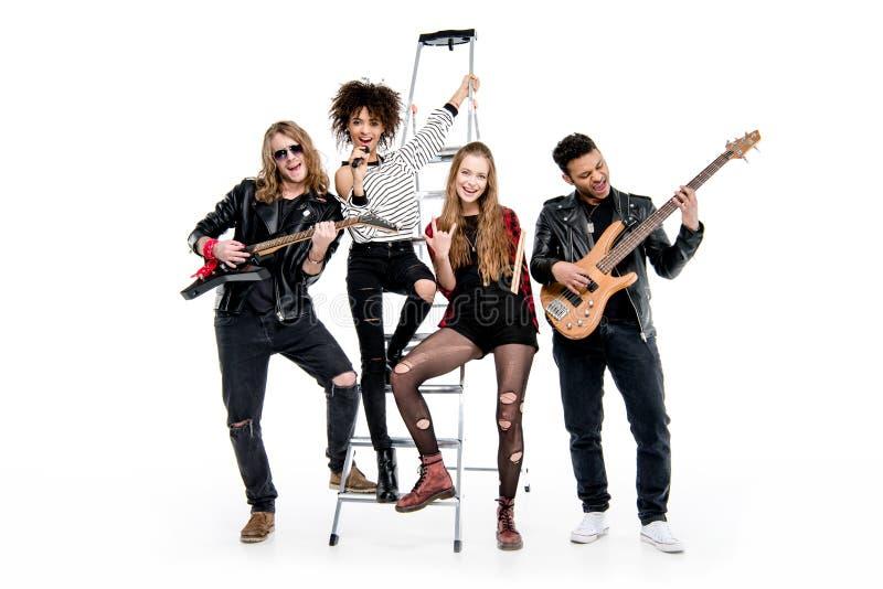 Banda de rock-and-roll joven que presenta con la escalera que sostiene el micrófono y las guitarras foto de archivo