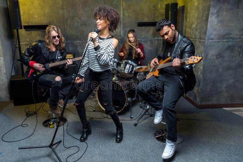 Banda de rock-and-roll multiétnica que ensaya en estudio musical fotografía de archivo